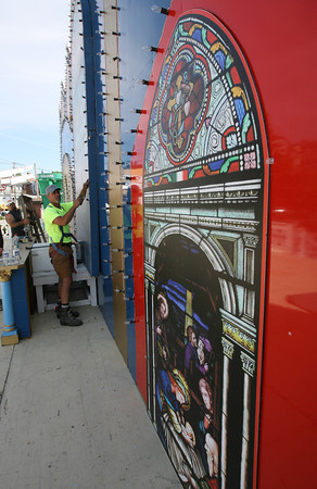 Scott Clayton replaces light bulbs on the altar in preparation for St. Peter's Fiesta, which starts today. The altar has new religious murals for this year's festivities. Photo by Kate Glass/Gloucester Daily Times