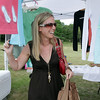 David Le/Gloucester Daily Times. Jessica Eddy, of Rockport, smiles as she looks through shirts and handmade clothes in a booth at the opening of the Cape Ann Farmer's Market at Stage Fort Park in Gloucester on Thursday afternoon. 6/30/11.