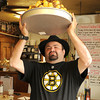 Gloucester:  Matt Legendado Groppo holds his own Stanley Cup or Stanley Cake over his head at George's Coffee Shop Friday afternoon.Made from 12 boxes of Twinkies 5 boxes of cup cakes 12 boxes of Cosmic Brownies and 1 pound of chocolate and weighing in at 35 LBS. He has it at George's Coffee Shop for all to see until it gets eaten on Saturday.Desi Smith/Gloucester Daily Times. June 12,2011
