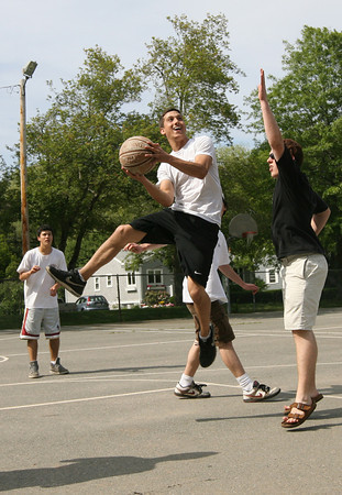 Noah Brown leaps in the air to get a shot while playing basketball at Sweeney Park with Mike Iwata, left, and Sean Terrill, right, yesterday afternoon. Photo by Kate Glass/Gloucester Daily Times