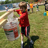 Seth Grover, a first grade student at East Gloucester Elementary School, pours a small bucket of water into a larger bucket as he and his teammates try to get it to weigh more than the bucket on the other side during field day on Thursday. Photo by Kate Glass/Gloucester Daily Times