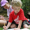 David Le/Gloucester Daily Times. Henry Coote, 5, of Manchester, draws a picture of an ambulance while being closely watched by his mother, Gail Coote, during a Poetry 'n Picnic event held outside Manchester Public Library. 6/27/11.