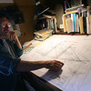 Leon Poindexter of Rockport looks over plans for the Beaver, which he is restoring at Gloucester Marine Railways for the Boston Tea Party Museum. Photo by Kate Glass/Gloucester Daily Times