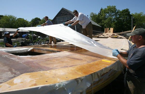 James Green, Harold Burnham, Chad Gadbois, and Chuck Redman lay fiberglass mesh over the deck of the Ardelle at Burnham's Boatyard yesterday afternoon.  Photo by Kate Glass/Gloucester Daily Times