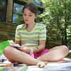 David Le/Gloucester Daily Times. Natalie Coopman, 10, of Manchester writes a poem while sitting on a picnic blanket outside Manchester Public Library on Monday morning. 6/27/11.
