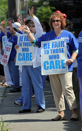 Francine Kace, right, and Christine Toomey, both nurses at Addison Gilbert Hospital, wave to supporters as they picket to push for contract guarantees to be included in any agreement to sell the hospital or merge with larger corporations. Photo by Kate Glass/Gloucester Daily Times