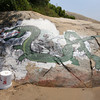 Jen Greeke of Gloucester repaints the sea serpent at Cressey's Beach, which has been covered over multiple times in the past several years. Greeke has contacted the city to try to get it sandblasted it will look more like the original serpent, which was painted by Robert Stevenson in 1955. Photo by Kate Glass/Gloucester Daily Times