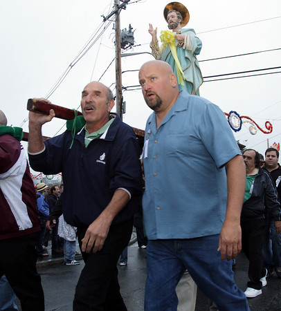 David Le/Gloucester Times. Sam PIzzimenti, left, and Warren Durgin, carry the statue of St. Peter on a short procession from St. Peter's Club to St. Peter's Square on Friday evening to kick off Fiesta 2011. 6/24/11.