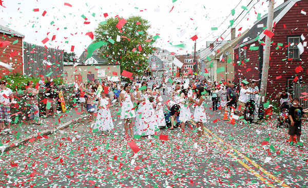 David Le/Gloucester Times. Confetti showers down on some members of the Fiesta Parade on Prospect Street as the statue of St. Peter is celebrated on Sunday afternoon. 6/25/11.