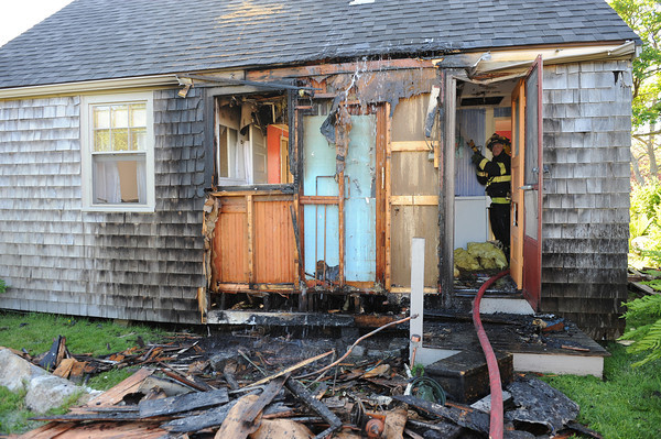 Rockport,  Firefighter Larry Libert hits a hot spot in a small cottage that caught fire around 4:23  Saturday afternoon.Desi Smith/Gloucester Daily Times.