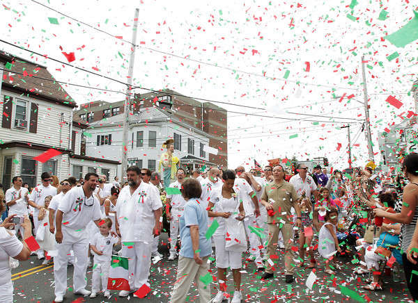 David Le/Gloucester Times. The statue of St. Peter is showered with confetti as it stopped at a house on Prospect St. during the Fiesta Parade on Sunday afternoon. 6/25/11.