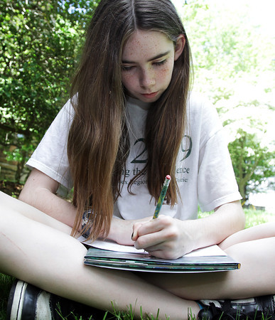 David Le/Gloucester Daily Times. Kelly Finnerty, 13, of Manchester writes a poem during Poetry n' Picnic, held outside the Manchester Library on Monday morning. 6/27/11.