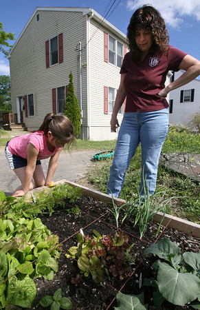 Linda Gross and her daughter, Jillian, 11, look over their garden that they started as part of the Backyard Growers program. Neither had much experience gardening, but Jillian wanted to start a garden after working in the one at West Parish Elementary School. Photo by Kate Glass/Gloucester Daily Times