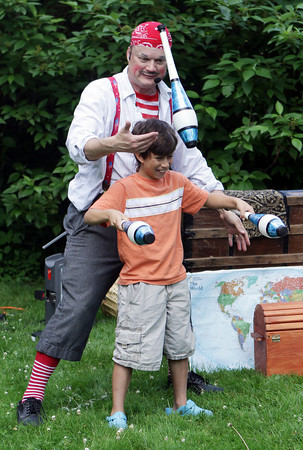 "David Le/Gloucester Daily Times. ""Awesome"" Robb Preskins gets a laugh from his audience as he gets the ""help"" of Anand Fedele, 9, of Rockport, to juggle a few batons during Preskins' Sky Pirate Show at Millbrook Meadow Park in Rockport on Wednesday afternoon. 6/29/11."