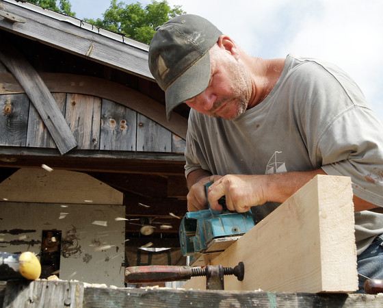 David Le/Gloucester Daily Times.  Chuck Redman, of Magnolia, trims down a plank of wood to get the right angle for the building of the Schooner Ardelle on Wednesday morning in preparation for the launch on July 9th. 6/29/11.