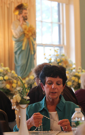 Marie Loiacano holds her rosary beads as she prays during the first day of St. Peter's Novena, unofficially marking the beginning of Fiesta, at the American Legion last night. Photo by Kate Glass/Gloucester Daily Times