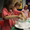 Willa Brosnihan, 8, mixes water and vinagar into a bag as part of an acid-base experiment during a chemistry club event at the Gloucester Library. Photo by Maria Uminski/Gloucester Daily Times