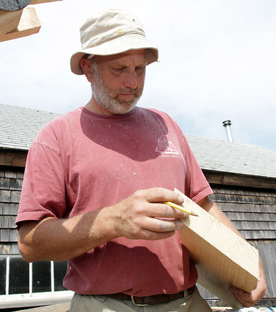 David Le/Gloucester Daily Times. Harold Burham of Burham's Boat Building takes some measurements for a piece of wood on Wednesday morning in preparation for the launch of the Schooner Ardelle on July 9th. 6/29/11.