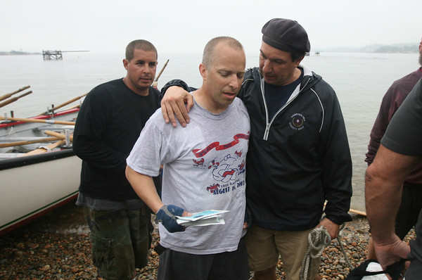 Andy Orlando, right, coach of Down 'N Dirty, chats with rower Billy Edmonds, who had to sit out part of the race due to a back injury. Orlando ended up rowing in his place from the Greasy Pole into shore. Photo by Kate Glass/Gloucester Daily Times