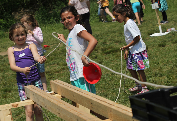 Alexa Clements, 1st grade, and Christina Ciaramitaro, 4th grade, pull a basket of cones during East Gloucester Elementary School's field day on Thursday. Photo by Kate Glass/Gloucester Daily Times