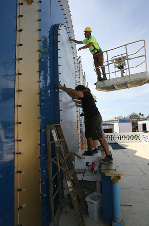 Scott Clayton secures the sky portion of the mural behind the altar with some help from people setting up the carnival during preparations for St. Peter's Fiesta, which starts today. Photo by Kate Glas/Gloucester Daily Times