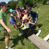 Ryan Argentino, a 4th grade student at East Gloucester Elementary School, reaches for a tube to place under Willow Barry as his team tries to move her across the grass without touching the ground during field day on Thursday. Photo by Kate Glass/Gloucester Daily Times