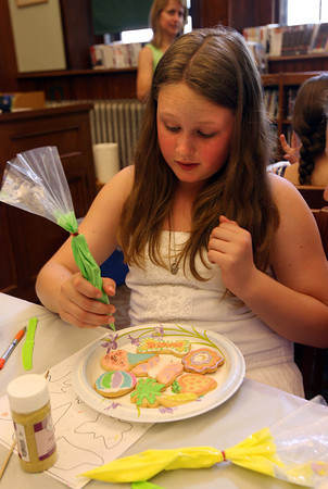 Manchester: Amber Shaw puts some finishing touches on cookies she decorated during a program with Deb Kaneb of Batter Up Bakery at the Manchester Public Library on Wednesday. Photo by Kate Glass/Gloucester Daily Times