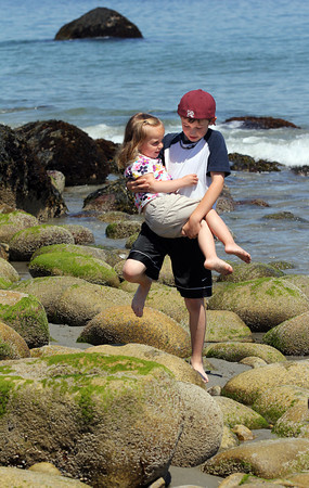 Rockport: Cal Twombly of Rockport carries his sister, Tessa, 3, across the rocks at Old Garden Beach so she would not hurt her feet. Photo by Kate Glass/Gloucester Daily Times