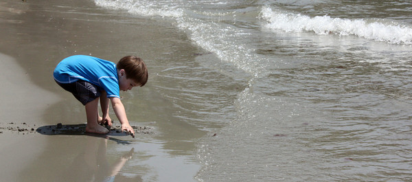 Gavin Kemps of Essex digs in the sand at White Beach on Thursday enjoying the sun. Photo by Maria Uminski/Gloucester Daily Times