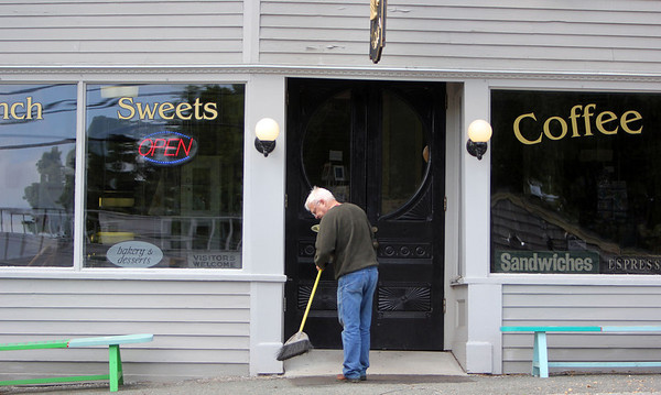 ALLEGRA BOVERMAN/Staff photo. Gloucester Daily Times. Essex: Nelson Emmons of Essex, co-owner of Village Market, sweeps the sidewalk in front of the shop on Monday afternoon.