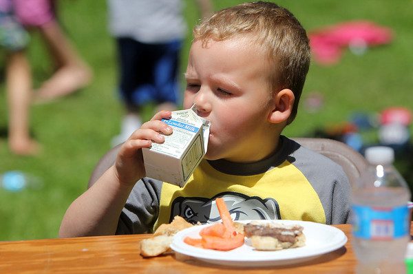 ALLEGRA BOVERMAN/Staff photo. Gloucester Daily Times. Gloucester: Brayden Melanson, 4, enjoys his milk while eating lunch during the Open Door Food Pantry Summer Lunch program held at Riverdale Park on Veterans Way on Friday afternoon.