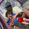 ALLEGRA BOVERMAN/Staff photo. Gloucester Daily Times. Gloucester: Tanner Smith, 3, and his dad Kevin Smith, both of Gloucester, slide together inside the Wizards' Wand at the carnival at Fiesta on Friday afternoon.