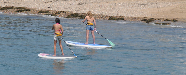 Gloucester: Two girls try their hand, and feet, at Stand Up Paddling or SUP off Pavilion Beach in Gloucester Wednesday afternoon. Jim Vaiknoras/staff photo