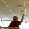 ALLEGRA BOVERMAN/Staff photo. Gloucester Daily Times. Gloucester: Ron Cunha, part of the city's maintenance team, adjusts the air conditioning vents at the Rose Baker Senior Center on Thursday. The center is a cooling station, but some of the vents had been pointed in a way made it a bit too cool for comfort for seniors coming in to beat the heat.
