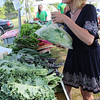 ALLEGRA BOVERMAN/Staff photo. Gloucester Daily Times. Gloucester: Kathleen Kipper of  Gloucester selected Chinese napa cabbage and then garlic scapes at Aprilla Farm of Essex during the first Cape Ann Farmers Market held at Stage Fort Park on Thursday afternoon. Elise Jillson, of the farm, is in the background.