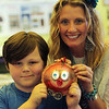 "ALLEGRA BOVERMAN/Staff photo. Gloucester Daily Times.  Gloucester: Gloucester Community Arts Charter School second grader Ethan Brien, left, and his art teacher Shay Cajolet, with his winning art piece in the All Kids Can Create Children's Art Exhibition sponsored by CVS/Caremark and the International Organization on Arts and Disability. Only the works of two students per state in grades K-13 are selected to travel the country for two years with other winning entries. This piece is titled ""Party Pig Dressed as a Bird,"" and is made with found objects from a ""treasure chest"" in the art room and a recycled paper plate. The mask is based on traditional Mexican coconut shell masks, which was part of a class project."