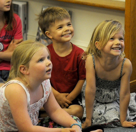 Essex: Kids laugh during the Great Big Planet presentation by Greg Nikitas at the Essex Library Tuesday night.  Nikitas used tale of the Old West and stories of about farming to give a message about conservation and taking care of the planet. JIm Vaiknoras/staff photo