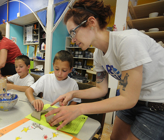 Gloucester: Aja Heussi works with Ryan Pireoni, 7, as he makes at Star Wars themed ceramic puzzle at Art Haven's Young Artists Workshops in Gloucester. About 2 dozen kids, including Ryan twin brother Jared , participated in the workshop held at the  Main Street non-profit. JIm Vaiknoras/staff photo