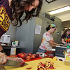 "ALLEGRA BOVERMAN/Staff photo. Gloucester Daily Times. Gloucester: During the ""Rainbow Warrior"" day at Veterans Memorial  Elementary School on Thursday, students sampled fruits and vegetables in a rainbow of colors and then charted their reaction to their taste, texture, crunch, juiciness and other criteria. Produce included grapes, peaches, cherry tomatoes and snow peas. The activity was part of the FoodCorps and CitySprouts food-related events that have been taking place all year at the school. Preparing more samples for students to try are, from left to right: Grace Cherubino, Erin Taylor and Sarah Rubin, who all run the program at the school."