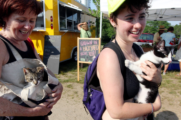 ALLEGRA BOVERMAN/Staff photo. Gloucester Daily Times. Gloucester: Julianne McKenney, left, and her daughter Lily Shaffer, right, both of Reading and summer residents of Gloucester, carry their cats Ketzelah, left, and his brother Rue, through the Cape Ann Farmers Market on Thursday afternoon while they were browsing. They didn't want to leave the cats in the car while it was so hot out.