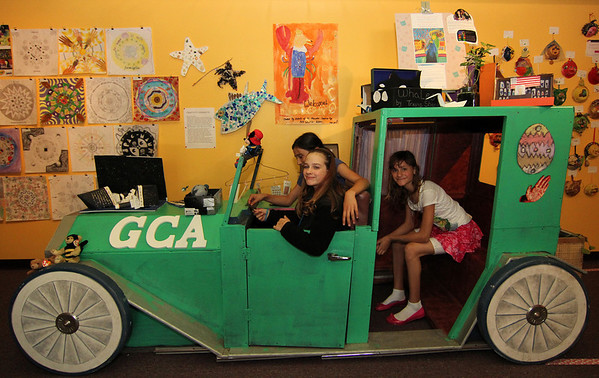 """ALLEGRA BOVERMAN/Staff photo. Gloucester Daily Times. Gloucester: The Gloucester Community Arts Charter School now has a fancy """"art car"""" parked in the main lobby. It was a prop from a 2007 production of """"Crazy for You"""" by the North Shore Music Theater and is a 16-foot long wood replica of a Rolls Royce. The roof is reinforced so it can be danced upon and five adults can fit inside it. The car has been gussied up by Charter School students and they can read, write, draw, act, play and hang out in it. Gordon Baird, on the board of trustees of the school, donated it to the school. Hanging out in it on Thursday are, in front, fourth graders Lillie Favazza, back, and Maddy Currier, and at right, fifth grader Emma Killian."""
