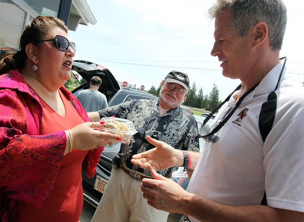 ALLEGRA BOVERMAN/Staff photo. Gloucester Daily Times. Gloucester: U.S. Sen. Scott Brown, right, arrives at Lobsta Land in Gloucester for lunch with various local leaders on Saturday. At left, Gloucester City Councilwoman Sefatia Romeo Theken welcomes him with some homemade Sicilian cookies. At center, rear, Louis Geoffrion of Manchester, looks on.
