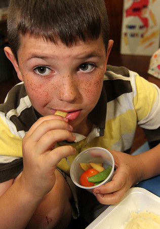 """ALLEGRA BOVERMAN/Staff photo. Gloucester Daily Times. Gloucester: During the """"Rainbow Warrior"""" day at Veterans Memorial  Elementary School on Thursday, students sampled fruits and vegetables in a rainbow of colors and then charted their reaction to their taste, texture, crunch, juiciness and other criteria. Produce included grapes, peaches, cherry tomatoes and snow peas. The activity was part of the FoodCorps and CitySprouts food-related events that have been taking place all year at the school. Danny Haserlat, a second grader, samples the peaches."""