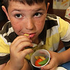"ALLEGRA BOVERMAN/Staff photo. Gloucester Daily Times. Gloucester: During the ""Rainbow Warrior"" day at Veterans Memorial  Elementary School on Thursday, students sampled fruits and vegetables in a rainbow of colors and then charted their reaction to their taste, texture, crunch, juiciness and other criteria. Produce included grapes, peaches, cherry tomatoes and snow peas. The activity was part of the FoodCorps and CitySprouts food-related events that have been taking place all year at the school. Danny Haserlat, a second grader, samples the peaches."