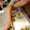 "ALLEGRA BOVERMAN/Staff photo. Gloucester Daily Times. Gloucester: During the ""Rainbow Warrior"" day at Veterans Memorial Elementary School on Thursday, students sampled fruits and vegetables in a rainbow of colors and then charted their reaction to their taste, texture, crunch, juiciness and other criteria. Produce included grapes, peaches, cherry tomatoes and snow peas. The activity was part of the FoodCorps and CitySprouts food-related events at the school. Reaching for a cup of colorful produce is third grader Ignazio LoContro."
