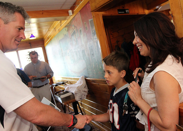 ALLEGRA BOVERMAN/Staff photo. Gloucester Daily Times. Gloucester: U.S. Sen. Scott Brown, left greets and then signs a photo for Dylan Leger, 9, of Ipwich, and his mom Lisa Marie Cashman, during Brown's visit to Lobsta Land in Gloucester on Saturday.