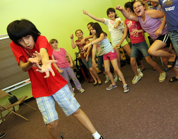 ALLEGRA BOVERMAN/Staff photo. Gloucester Daily Times. Gloucester: Julian Mendoza, far left, a seventh grader at Gloucester Community Arts Charter School, rehearses his piece for the upcoming school talent show as classmates dance behind him. There are 27 acts - students and teachers are participating -  for the talent show, which will be held on Wed. June 6 from 7-8:30 p.m in the school gymnasium.