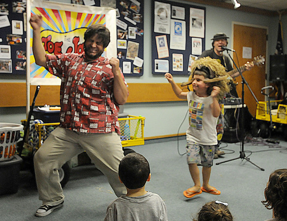 Gloucester: Vinny Lovegrove of The Toe Jam Puppet Band dances like a monkey with Gavin Natti, 5, at the Sawyer Free Library in Gloucester Tuesday morning.Tom Poitras plays guitar in the background JIm Viknoras/staff photo