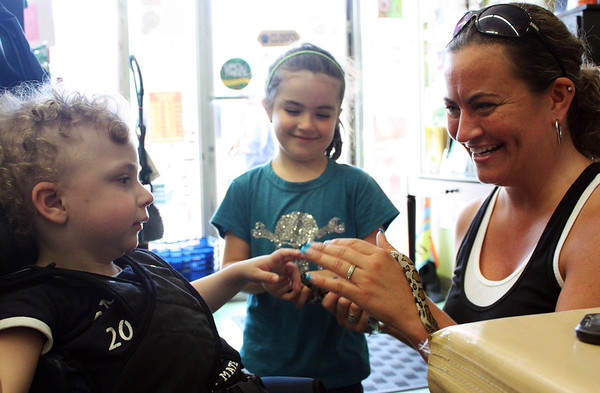 Siblings Andrew and Kyla Forsyth, 3 and 5 respectively, of Gloucester, pet eastern milk snakes with their mother Caroline at Animal Krackers in downtown Gloucester during Caring for Your Snakes with Rick Roth put on by Cape Ann Vernal Pond Team. Photo by Maria Uminski/Gloucester Daily Times