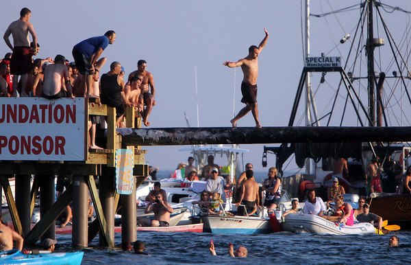 ALLEGRA BOVERMAN/Staff photo. Gloucester Daily Times. Gloucester: Ross Carlson on the Greasy pole just before he reached the flag and won the third round of the Friday Greasy Pole event.